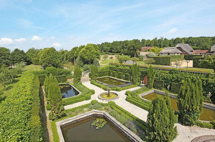 Lush gardens surround the entire property, beginning within the horseshoe of the main house and extending southward, comprising of mature herbaceous borders and a topiary knot garden