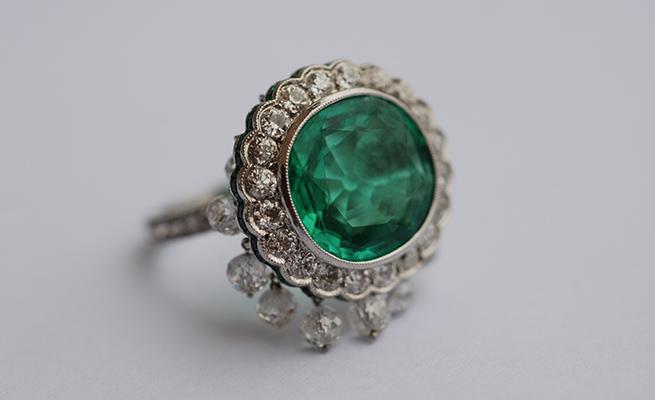 Old mine-cut emerald 7.69 karats set in platinum with hanging diamond beads, 5.48 karats